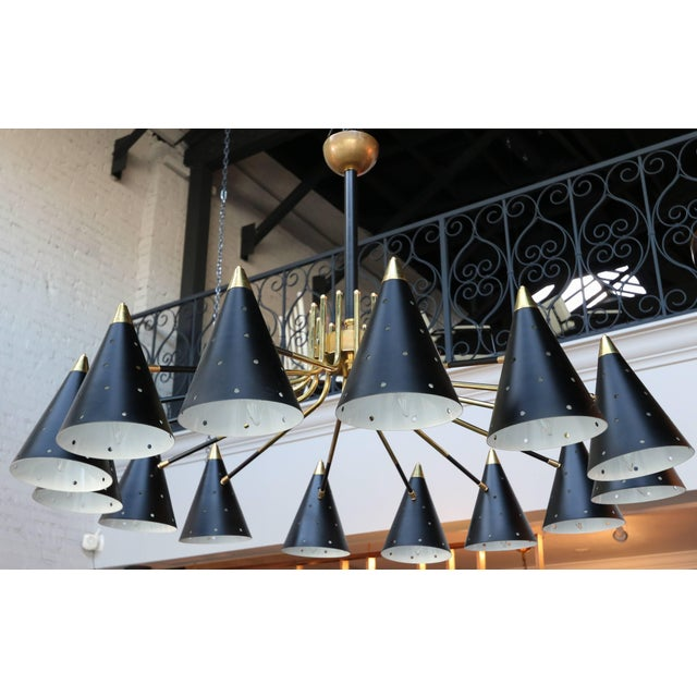 Midcentury style brass chandelier with 14 black perforated shades. Available Now