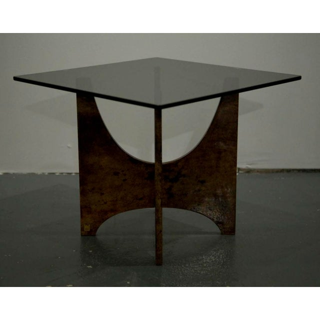 A square occasional table composed of a smoked glass top raised on two goat skin wrapped wood interlocking panels by Aldo...