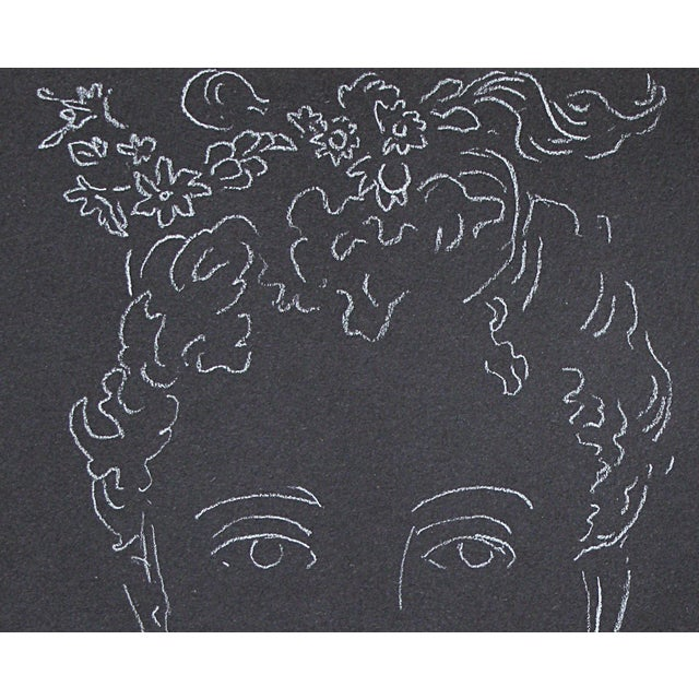 Drawing of a woman in white charcoal on dark paper. Her knot of hair holds a delicate spray of flowers, behind her an urn...
