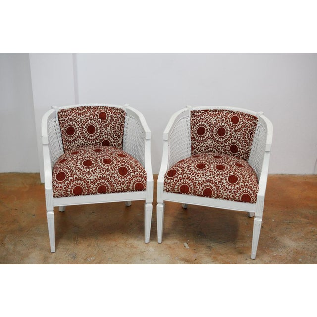 Pair of 60's era side chairs with distressed white paint and partial caned backing. Reupholstered with a rust and dark...