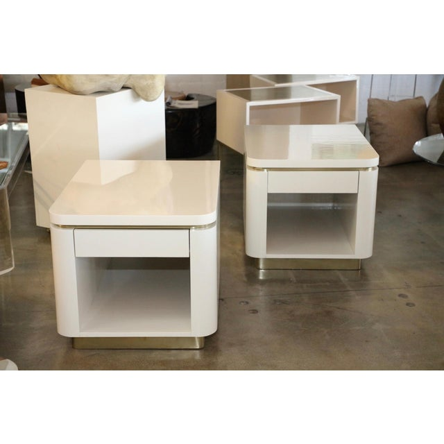 A pretty pair of Steve Chase designed nightstands or end tables. They are finished in ivory lacquer and brass. The brass...