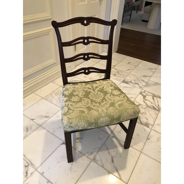 Set of 6 Chippendale Style dining chairs featuring carved ribbon ladder backs and upholstered seats. The set consists of...
