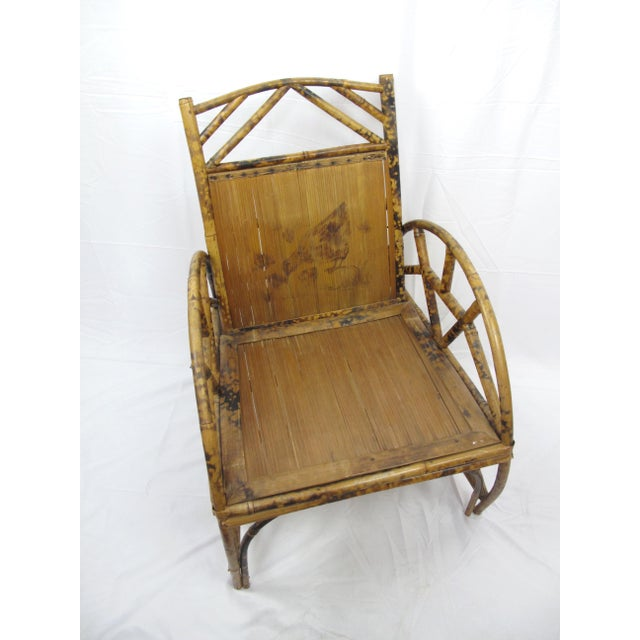 Early 20th century Chinese bamboo chair with ink painting of a mother hen and chick upon the back rest. The chair measures...