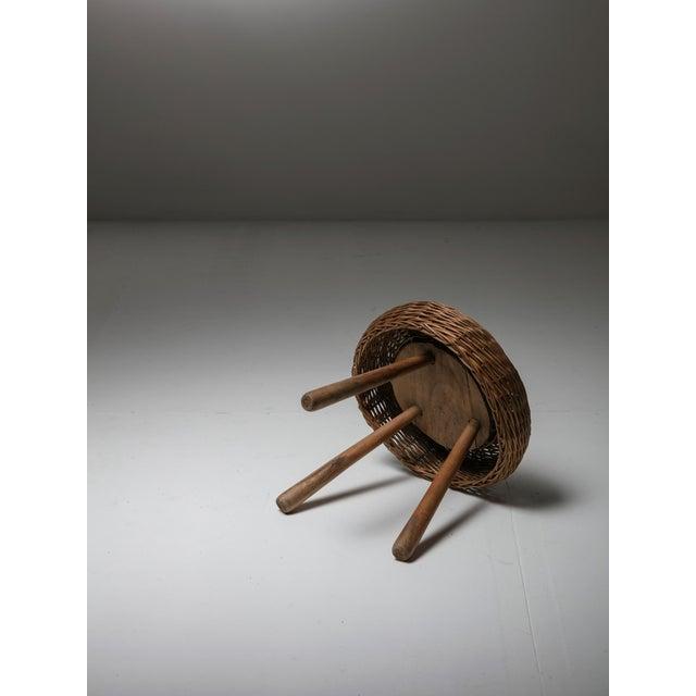 Round wicker stool with three legs.