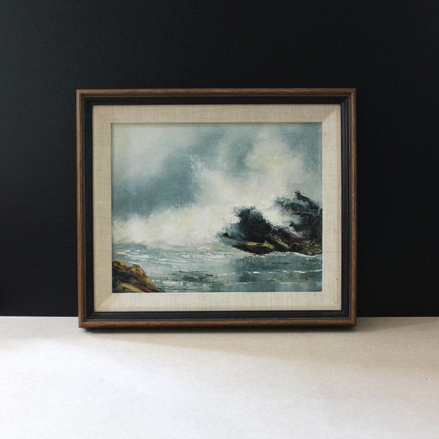 """This is a small, beautiful oil painting of the California coast with ocean waves crashing on rocks, signed """"Lue Bloedon.""""..."""