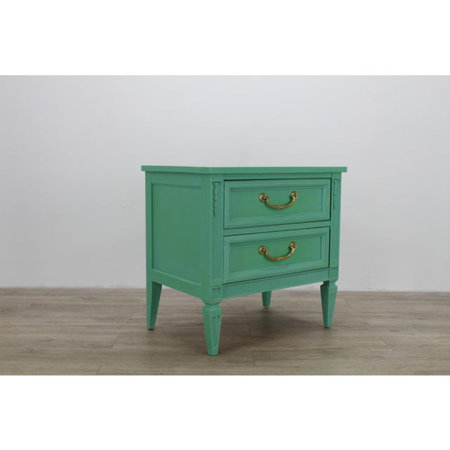 Mid-century neoclassical-style two-drawer nightstand nicely painted in pastel with distressed finish and gold painted...