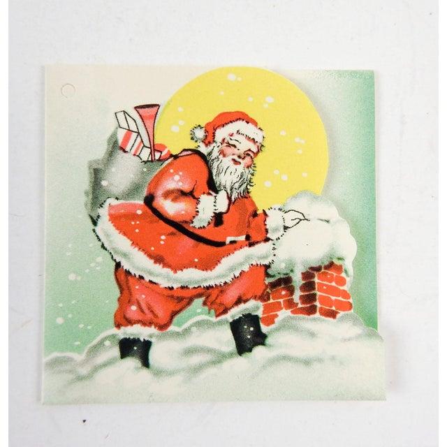 Set of 3 circa 1950's bridge tally cards, unused. Die cut design of Santa at the chimney, with silk tassels.
