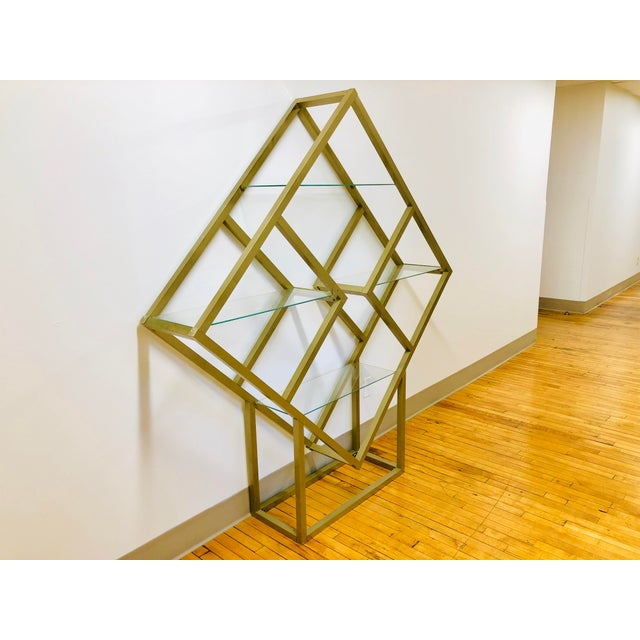 Brass-colored metal and glass etagere attributed to Milo Baughman. This incredible geometric shelving unit features four...