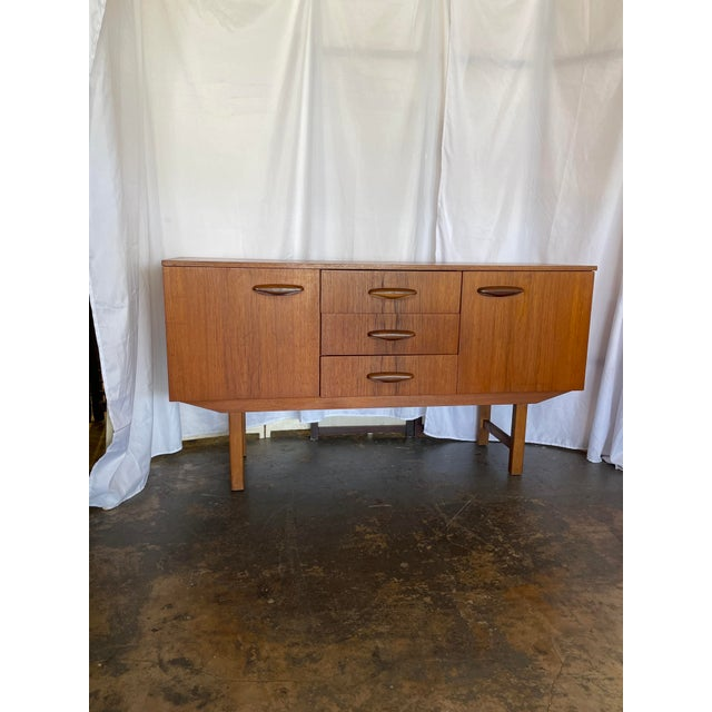 A small teak credenza with sculpted pulls, (3) center drawers and cabinet doors on either side for storage. Right side has...