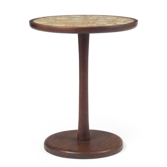 A pedestal side table with a round top inlayed with multi-toned oatmeal colored circular ceramic tiles in various sizes,...