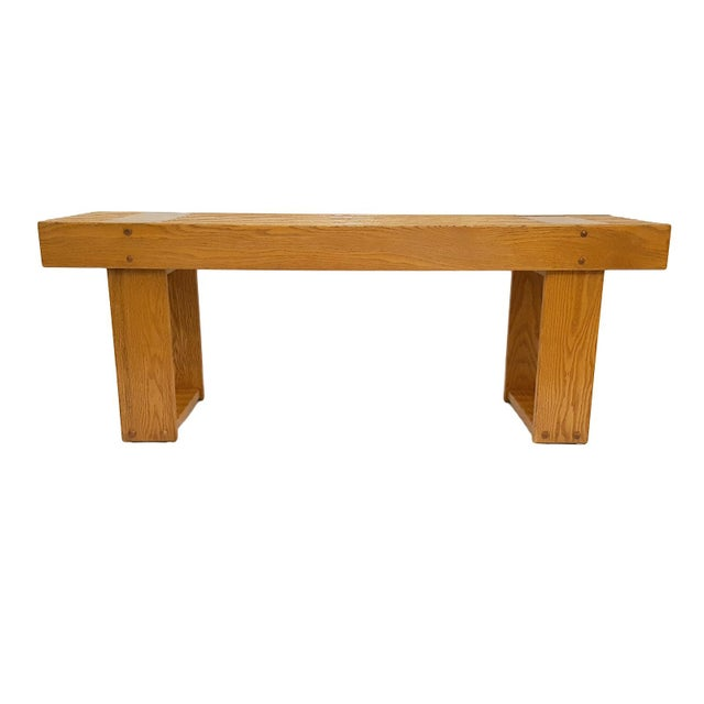A mid-century modern heavy oak slat bench. This is a sturdy well-made piece. It's heavy at approximately 50 lbs. The bench...