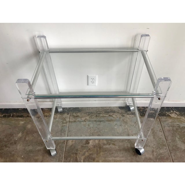 Vintage lucite bar cart with 2 glass shelves. The cart rolls smoothly on casters. Small brass hardware throughout.