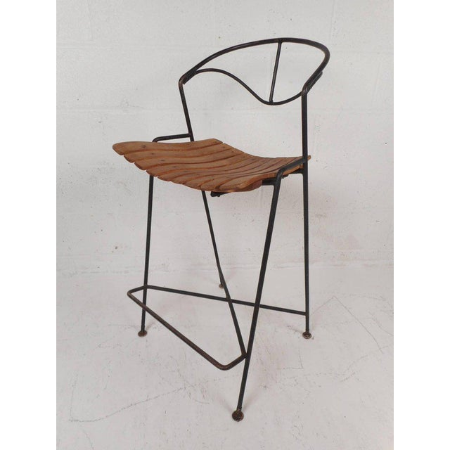 This beautiful set of three vintage modern bar stools feature a slatted seat and a sculpted wrought iron backrest....