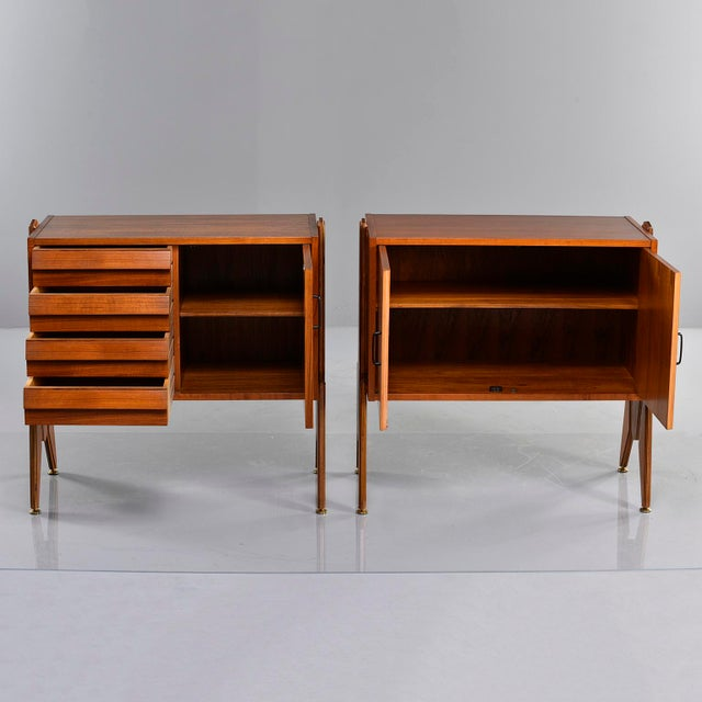 Circa 1970s pair of Italian teak side cabinets have interesting side mounted legs/supports that allow for height range...