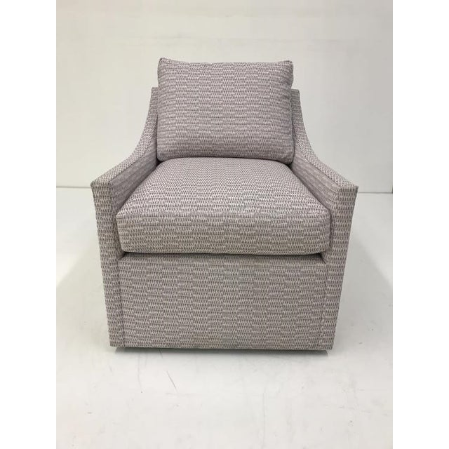 The Truman Swivel Chair is a first quality showroom sample that features a purple fabric with a loose pillow back.