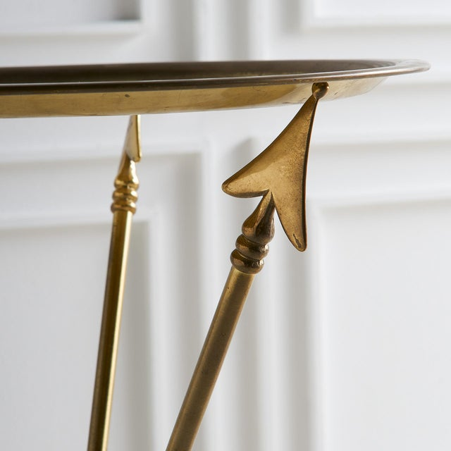 A simple, elegant and stylish European Brass Tripod table featuring an arrow motif and a removable tray top table.