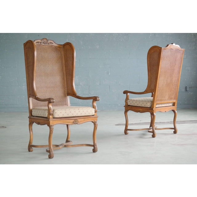 Super stylish pair of 1920s American Hollywood Regency tall wingback chairs in rare double cane. The chairs show...