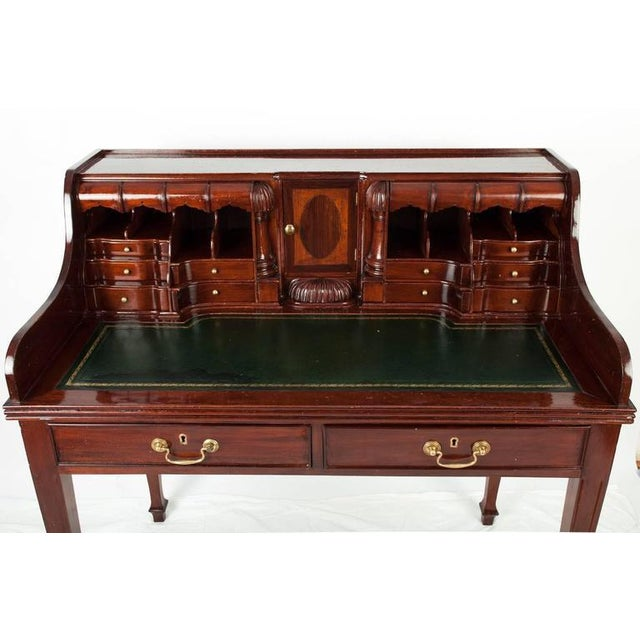 Vintage secretary with embossed leather top, several storage compartments, and two main drawers.