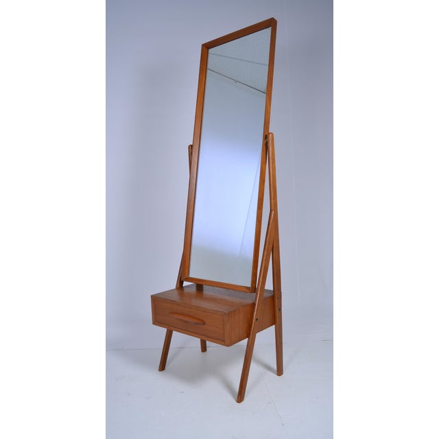 "Teakwood mirror on stand with single drawer beneath. Marked ""Made in Denmark."" Great form and size."