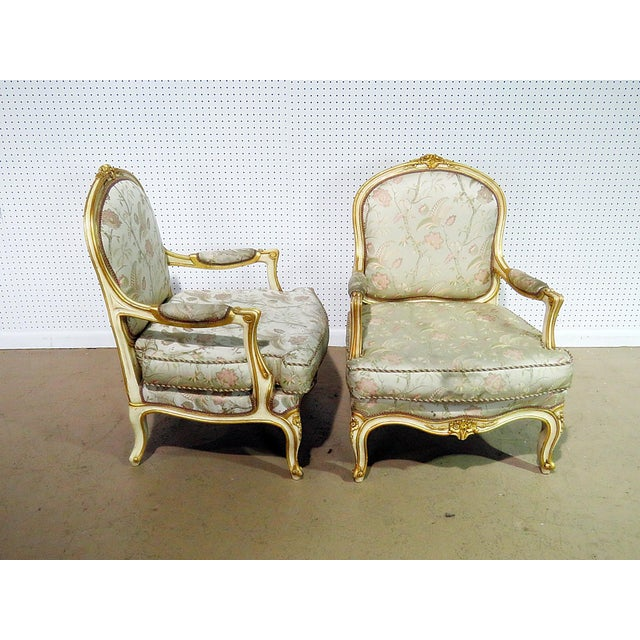 Pair of Louis XV style distressed painted fauteuils with gilt trim.