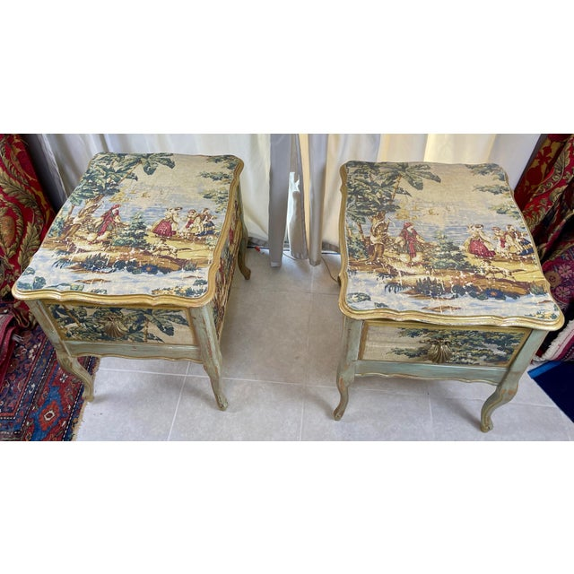 Beautiful pair of nightstands decoupaged with fabric depicting idyllic scene. Gorgeous brass sea shell pulls!