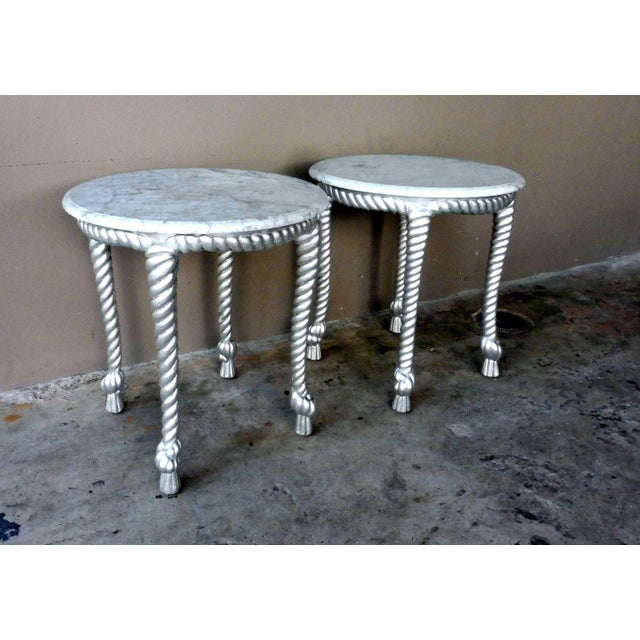 This is a pair of Hollywood regency tables from the 1970s. The pieces feature marble tops and silver leafed, twisted rope...