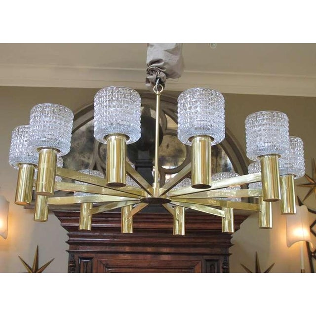 A stylish and large-scaled Swedish 1960's brass and crystal 12-arm chandelier by Carl Fagerlund for Orrefors; the central...