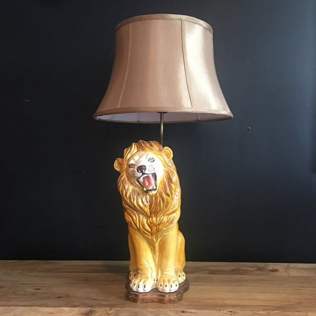 A rare Italian hand-painted porcelain lion mounted on wooden base with a tulip silk shade. This large roaring lion is in...