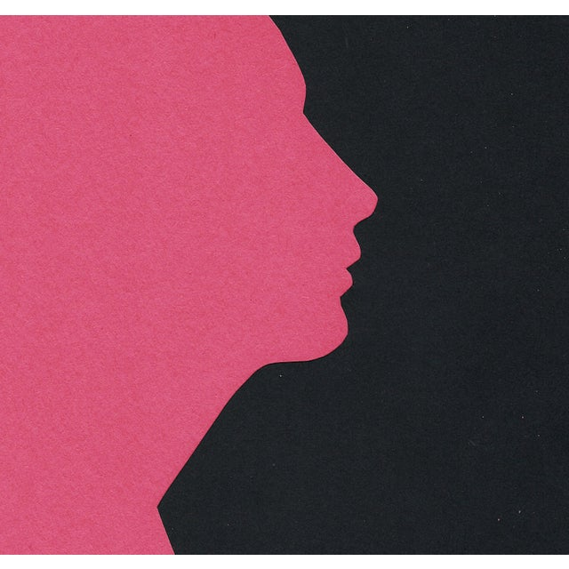 Minimal profile of a woman in deep red-pink and black. The outline of her silhouette is created by the cut void in the...