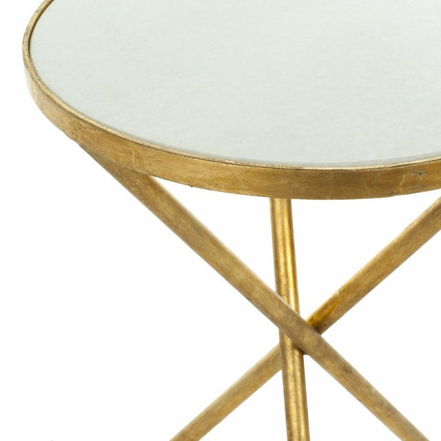 The diminutive Marcie accent table is functional and decorative beside a chair, with round white granite top set in an...