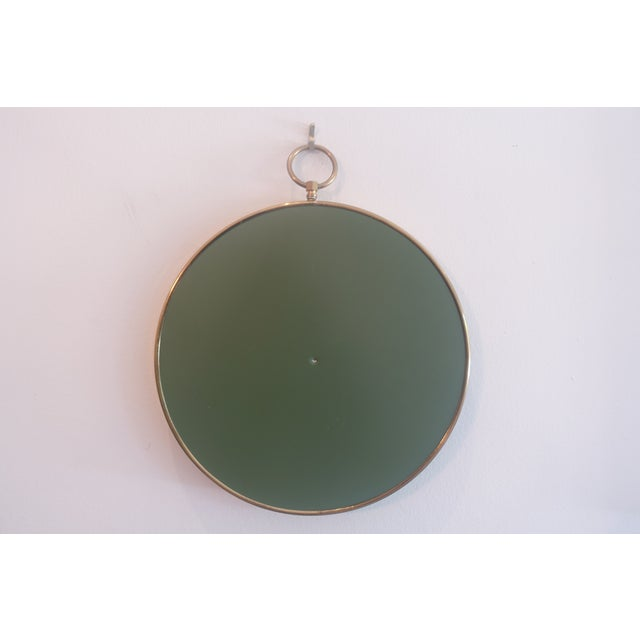 Mid Century Modern round brass frame mirror in the style of Fornasetti.