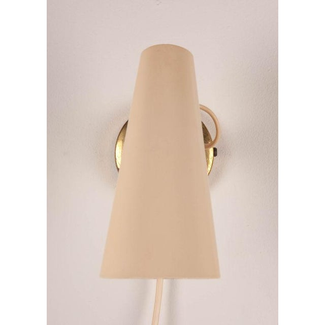 A pair of wall lights each with a brass canopy supporting an adjustable, off-white enameled metal cone shaped shade and...