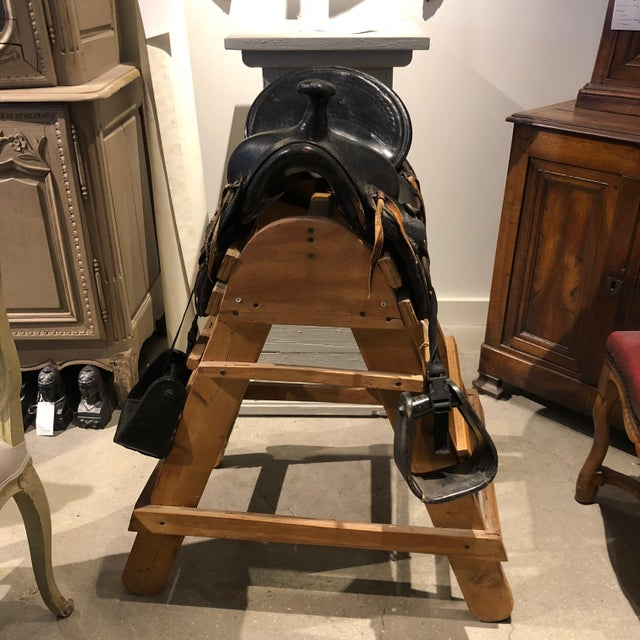 20th century nicely tooled leather saddle and rustic wood stand. Both saddle and stand in fine condition. Child's western...