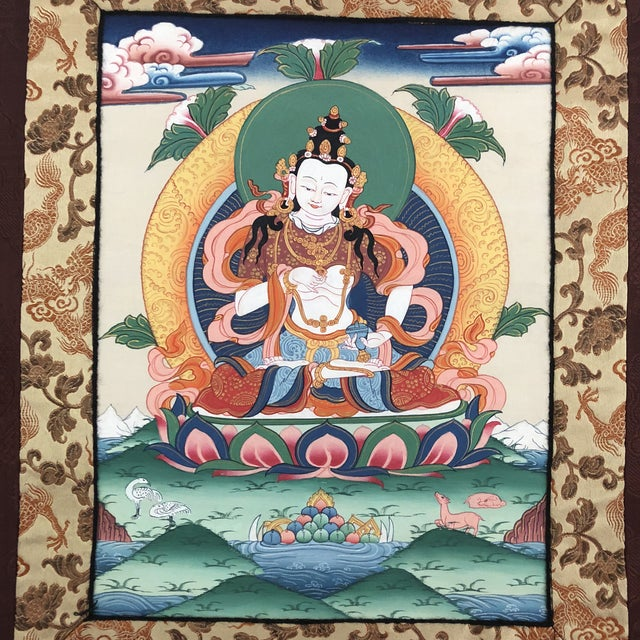This small burgundy silk Thangka (see below) depicts a ceremonial image - colorfully hand painted by Buddist monks and is...