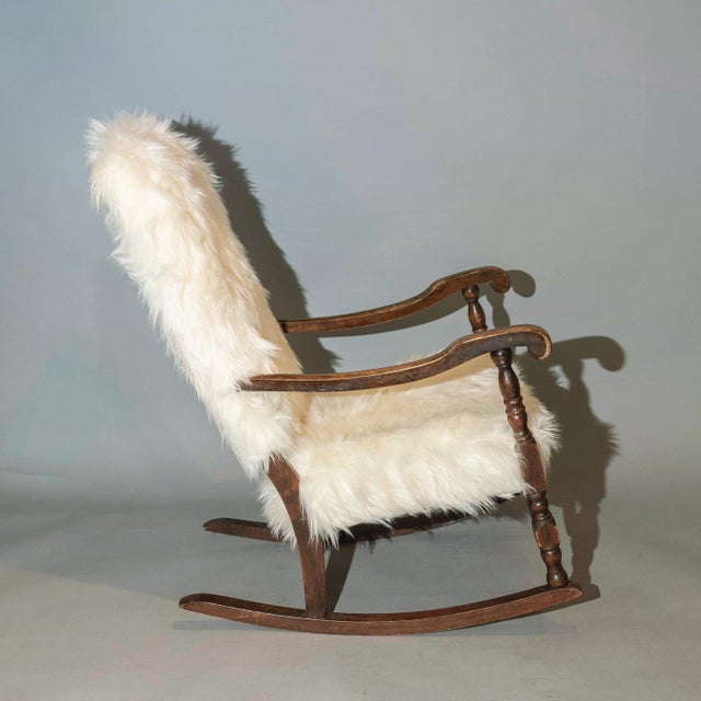 Traditional curated French rocker chair with mahogany wood & new Mongolian faux fur in off-white shade. Heavy and sturdy...