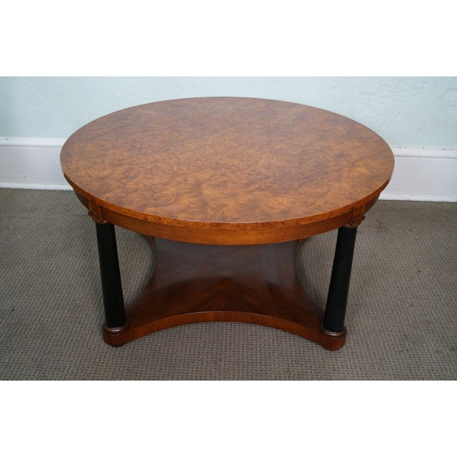 Vintage Italian round burl wood Biedermeier style coffee table. Features burl wood top and ebonized column support....