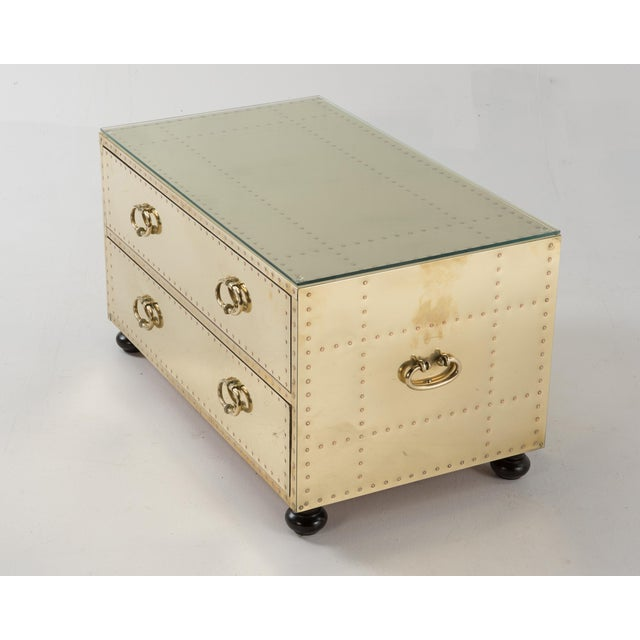 Sarreid brass clad two-drawer cabinet with bun feet and custom glass top, made in Spain, 1970s. This versatile piece can...