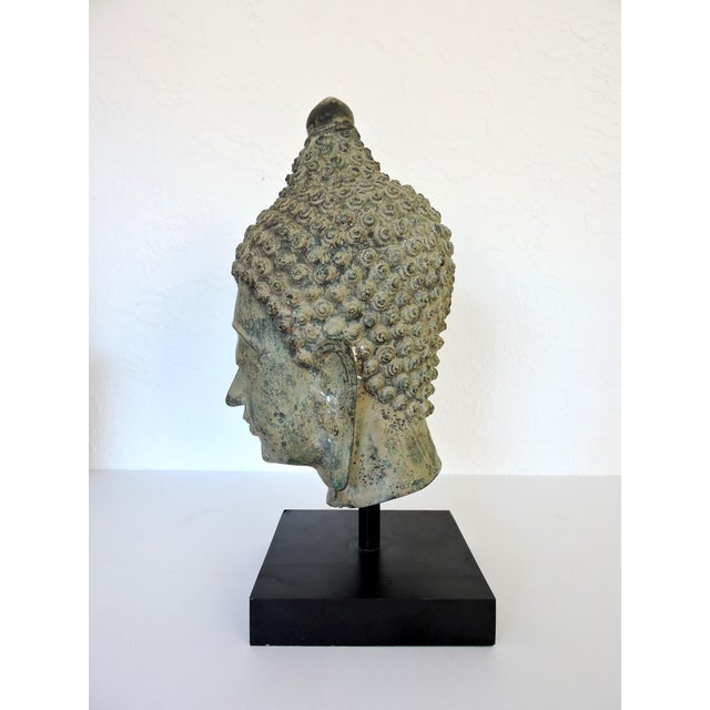Facial representation of Buddha mounted on a black plinth/stand. This is a highly detailed Buddha head in the traditional...