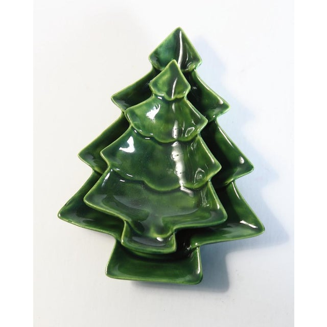 A small pair of ceramic nesting Christmas trees. Evergreen color. Great for your Holiday décor. Can be used as candy dish...