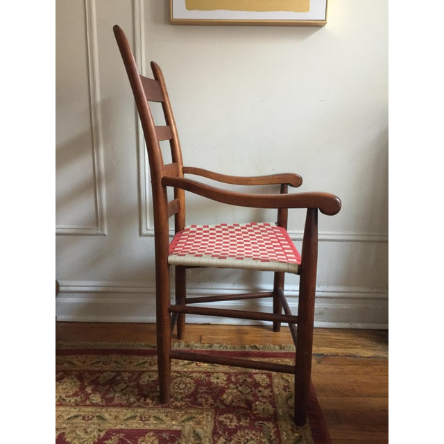 This wooden Shaker style ladder back accent chair features a woven cloth fabric seat in a red and white checkered pattern....