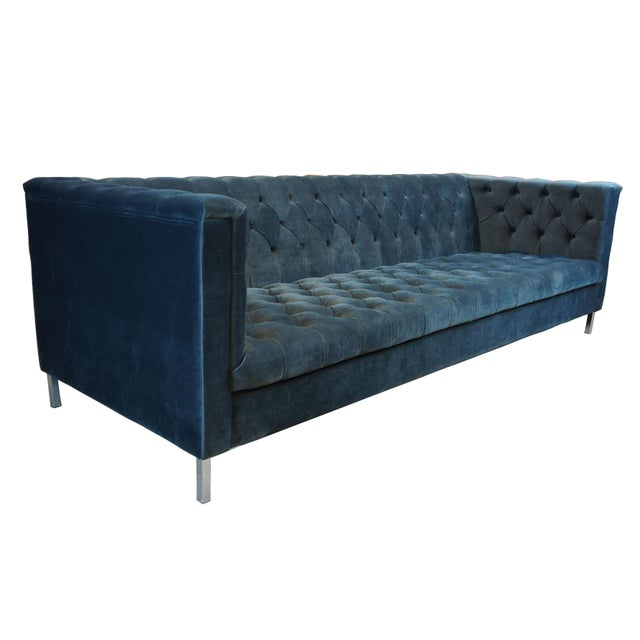 A lavish blue button tufted velvet sofa with chrome legs. A stylish yet comfy addition to any room