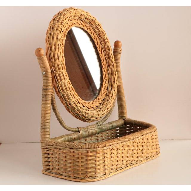 Tilting wicker mirror with handy integrated basket for storing make up or jewelry.