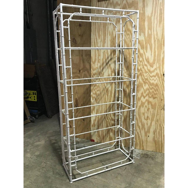 "Large faux bamboo iron étagère in white, substantial casting, fitted with four glass shelves. Measures: 14.5""x 33.5""."