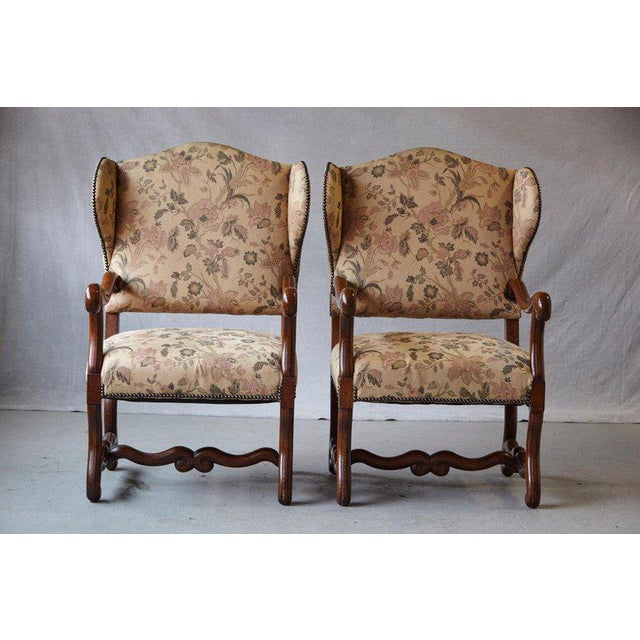 Striking pair of antique French Louis XIV style, walnut wingback fauteuils with carved armrests, standing on 'os de...