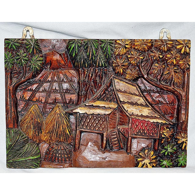 A fun, solid teak hand carved wall plaque depicting an Indonesian beach scene. Hand painted finish.