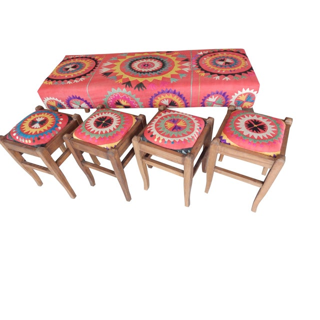 Colorful round ottoman upholstered with vintage Uzbek suzani fabric. This one-off bench has been lovingly restored with...
