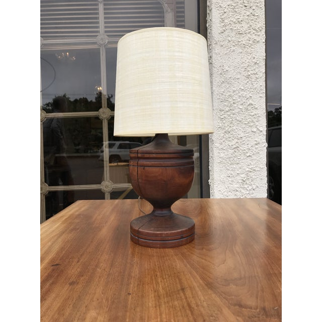 Small wooden urn lamp with off- white drum shade.