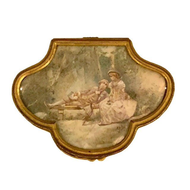 A late 19th century neo classical bronze ormolu box French with a bone painted top protected by glass that is beveled. The...