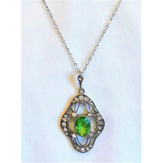 The early 1900s 800 silver lavaliere pendants set with an oval faceted peridot paste stone surrounded with smaller clear...