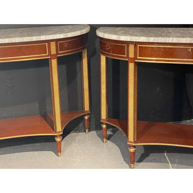 Pair of Russian neoclassical demilune marble top consoles, sideboards or sofa tables having a tortoiseshell Veneer Finish....